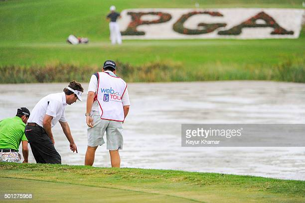 Michael Letzig assists the caddie of David Pastore after he hit his second tee shot into the water from the drop zone on the 17th hole of the...