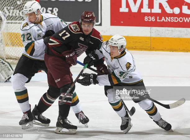 Michael Little of the Peterborough Petes battles between Antonio Stranges and Alec Regula of the London Knights in an OHL game at the Peterborough...