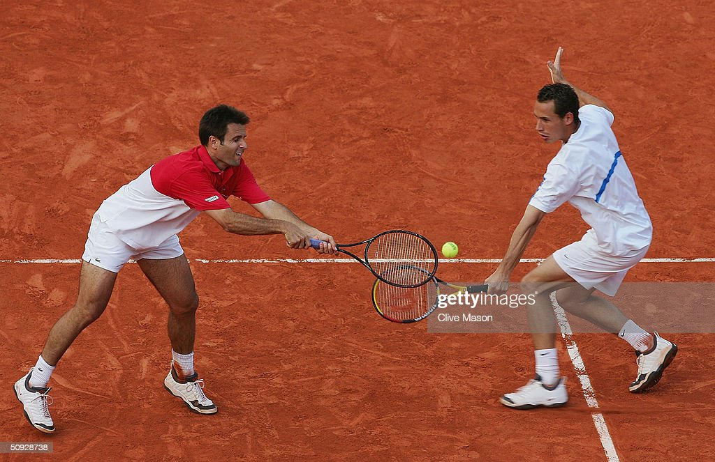 Michael Llodra and Fabrice Santoro of France return serve in their mens doubles final match against Xavier Malisse and Olivier Rochus of Belgium, during Day Thirteen of the 2004 French Open Tennis Championship at Roland Garros on June 5, 2004 in Paris, France.