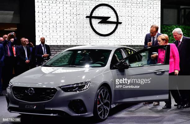 Michael Lohscheller CEO of Opel shows an Opel car to German Chancellor Angela Merkel and Hesse's State Premier Volker Bouffier during the official...