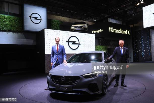 Michael Lohscheller chief executive officer of Adam Opel AG left and Carlos Tavares chief executive officer of PSA Group pose for photographs beside...