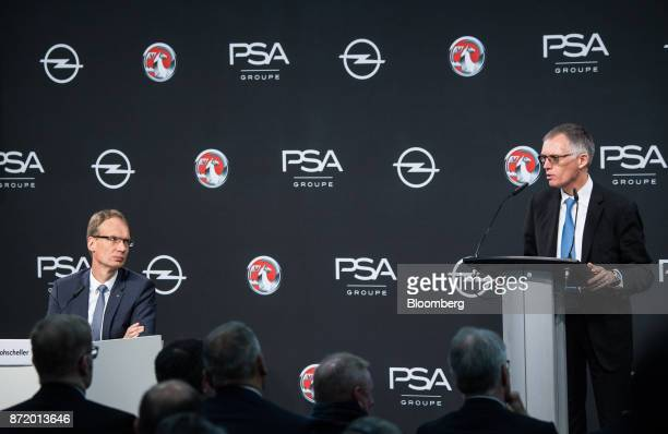 Michael Lohscheller chief executive officer of Adam Opel AG left looks on as Carlos Tavares chief executive officer of PSA Group speaks during a news...