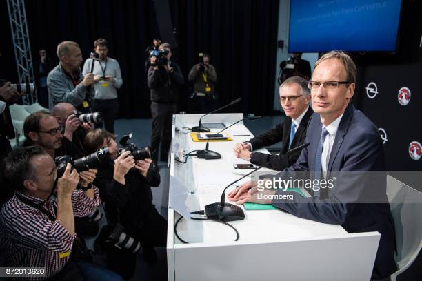 Michael Lohscheller chief executive officer of Adam Opel AG right and Carlos Tavares chief executive officer of PSA Group pose for photographers...