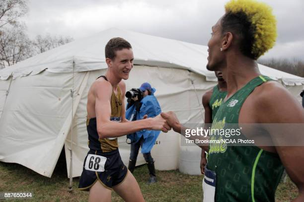 Michael Lowrie of California Baptist University shakes hands with Elias Gedyon of Adams State University during the Division II Men's Cross Country...