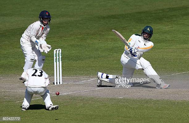 Michael Lumb of Nottinghamshire sweeps with Alex Davies of Lancashire looking on as Haseeb Hameed takes cover during day three of the Specsavers...