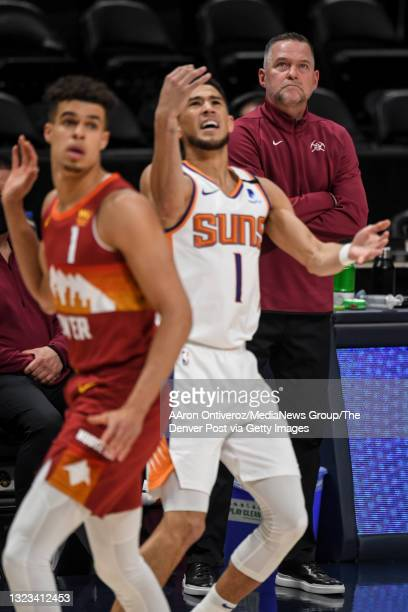 Michael Malone head coach of the Denver Nuggets watches as Devin Booker of the Phoenix Suns looks for a foul after shooting over Michael Porter Jr....
