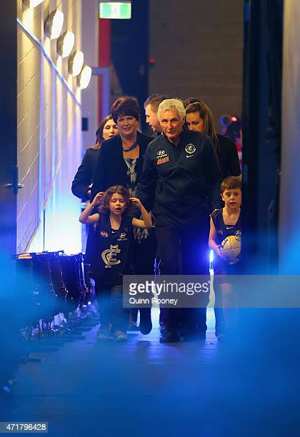 Michael Malthouse the coach of the Blues walks out onto the field with his grandchildren during the round five AFL match between the Carlton Blues...