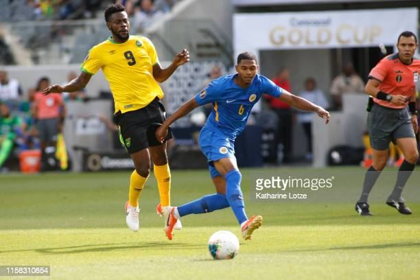 Michael Maria of Curacao passes the ball as Ricardo Morris of Jamaica follows during the first half of the Jamaica v Curacao Group C 2019 CONCACAF...