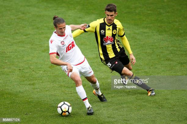 Michael Marrone of Adelaide United holds off the challenge of Dario Vidosic of the Phoenix during the round one ALeague match between Wellington...