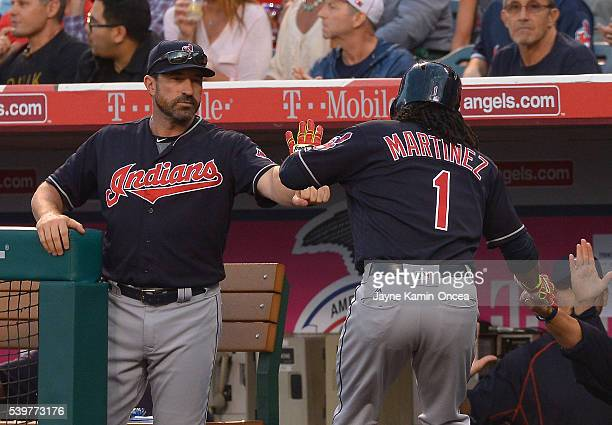 Michael Martinez of the Cleveland Indians is greeted at the dugout by pitching coach Mickey Callaway of the Cleveland Indians after scoring a run in...