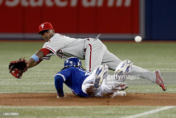 Michael Martinez of the Philadelphia Phillies dives to stop a home plate missed throw to catch Colby Rasmus of the Toronto Blue Jays on a lead off...