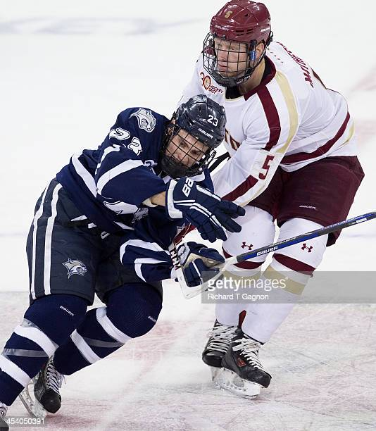 Michael Matheson of the Boston College Eagles checks Kyle Smith of the New Hampshire Wildcats during NCAA hockey action against the New Hampshire...