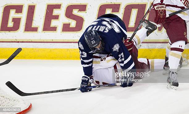 Michael Matheson of the Boston College Eagles is checked by Kyle Smith of the New Hampshire Wildcats during NCAA hockey action against the New...