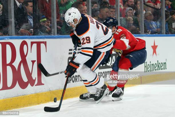 Michael Matheson of the Florida Panthers attempts to take the puck from Leon Draisaitl of the Edmonton Oilers at the BBT Center on March 17 2018 in...