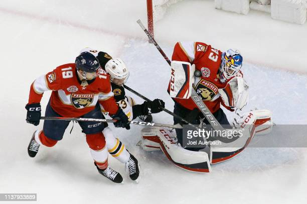 Michael Matheson of the Florida Panthers defends against Karson Kuhlman of the Boston Bruins as goaltender Samuel Montembeault makes a chest save...