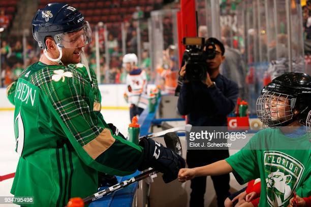 Michael Matheson of the Florida Panthers knuckle bumps fans sitting on the bench while wearing St Patricks Day warm ups prior to the start of the...