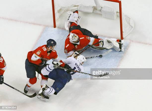 Michael Matheson of the Florida Panthers takes Zach Hyman of the Toronto Maple Leafs to the ice as Goaltender Roberto Luongo stops his shot at the...