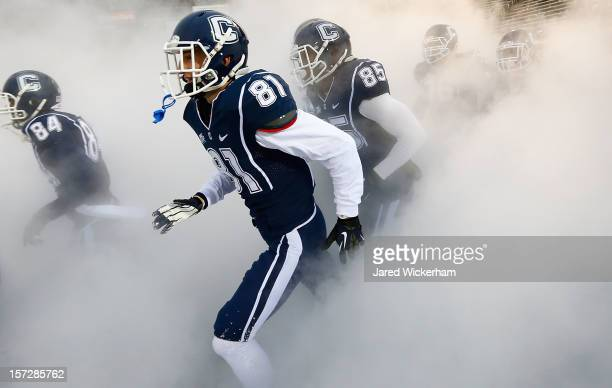 Michael Matson of the Connecticut Huskies runs onto the field with his teammates prior to the game against the Cincinnati Bearcats during the game at...