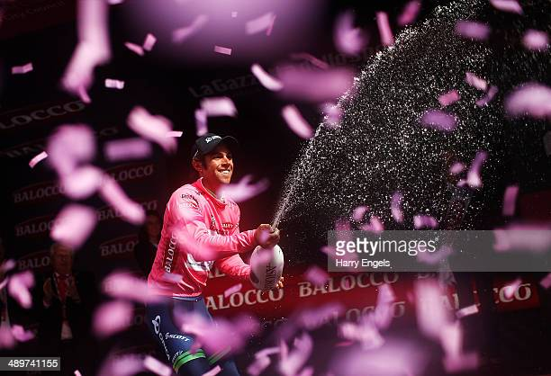 Michael Matthews of Australia and team OricaGreenEDGE sprays champagne in celebration after retaining the Maglia Rosa jersey following the third...