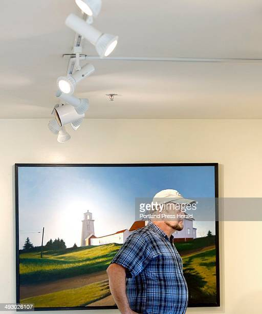 Michael Mayhew looks at paintings in Gleason Fine Art in Boothbay Harbor on July 8, 2013. With the help of Mayhew, Gleason Fine Art replaced their...