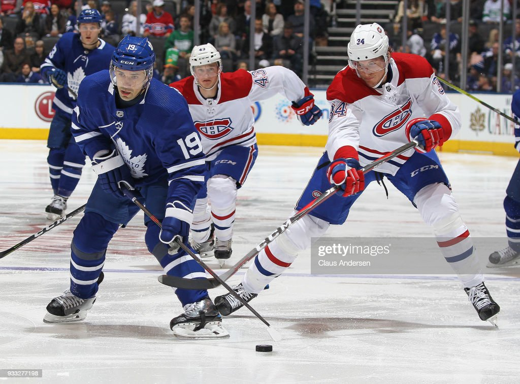 Michael McCarron #34 of the Montreal Canadiens tries to check Tomas Plekanec #19 of the Toronto Maple Leafs during an NHL game at the Air Canada Centre on March 17, 2018 in Toronto, Ontario, Canada. The Maple Leafs defeated the Canadiens 4-0.