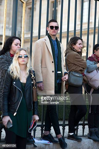 Michael McGann wears tan overcoat, and Saint Laurent scarf before Dior at Cour Carree Du Louvre during Paris Fashion Week Spring/Summer 2016 on...