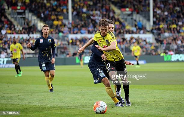 Michael McGlinchey of the Wellington Phoenix controls the ball despite the attention of Storm Roux of the Central Coast Mariners during the round 17...