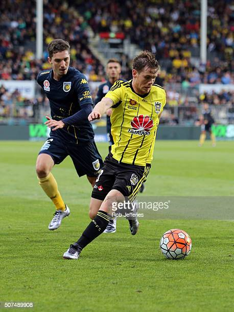 Michael McGlinchey of the Wellington Phoenix controls the ball despite the attention of Jacob Poscoliero of the Central Coast Mariners during the...