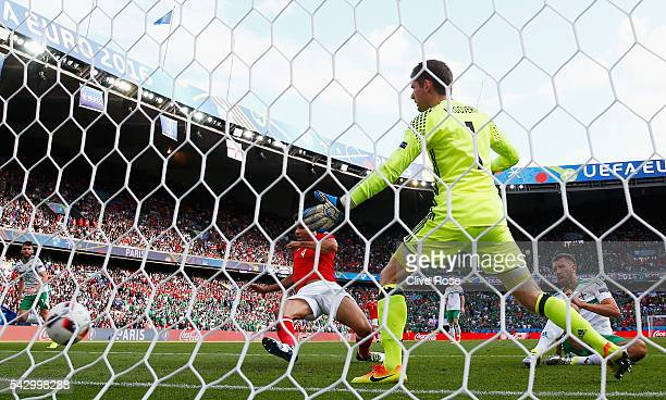 Michael McGovern of Northern Ireland watches the ball as his team mate Gareth McAuley scores an own goal during the UEFA EURO 2016 round of 16 match...