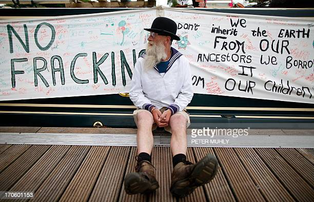 Michael McIntyre from Enniskillen sits beside his boat with an antifracking banner in Enniskillen Northern Ireland on June 15 2013 McIntyre will be...