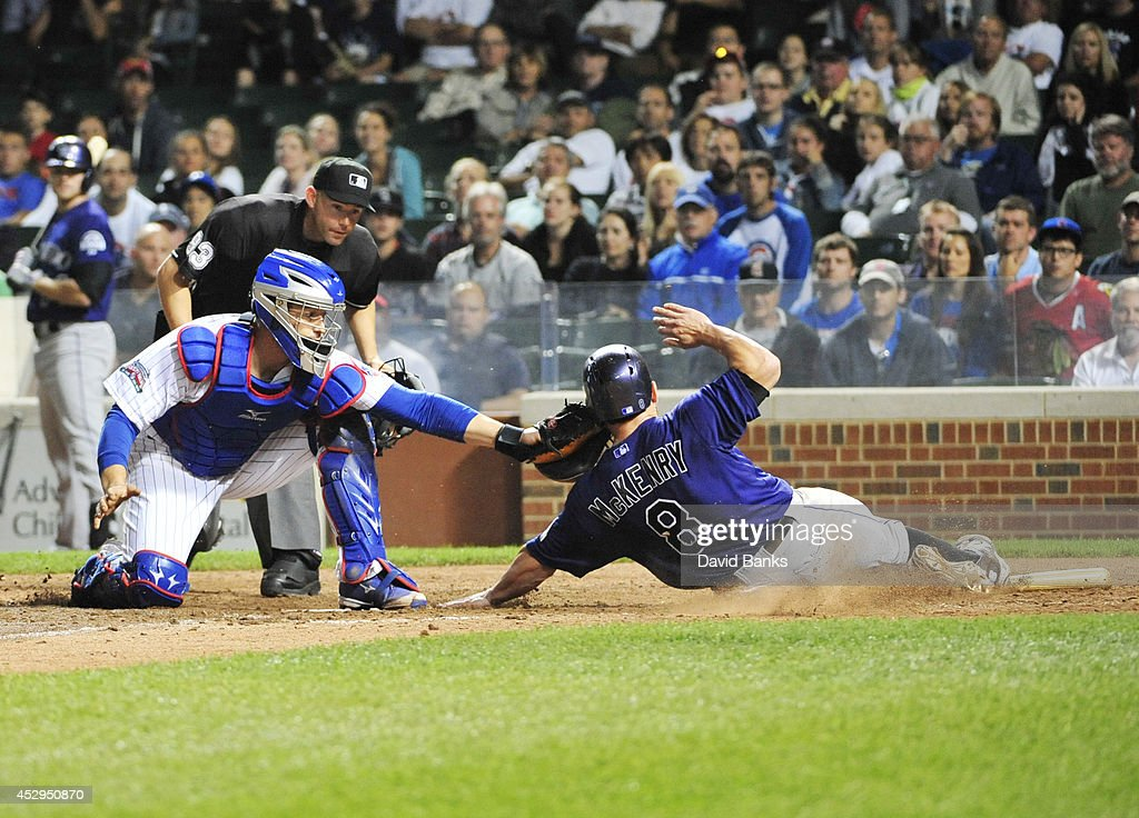 Michael McKenry #8 of the Colorado Rockies is tagged out by John Baker #12 of the Chicago Cubs during the tenth inning on July 30, 2014 at Wrigley Field in Chicago, Illinois.