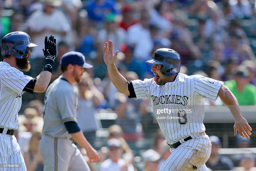 Michael McKenry #8 of the Colorado Rockies reacts after scoring on a base hit by Ben Paulsen (not pictured) and celebrates with Charlie Blackmon #19 as relief pitcher Michael Blazek #54 of the Milwaukee Brewers walks back to the mound during the seventh inning at Coors Field on June 20, 2015 in Denver, Colorado. The Rockies defeated the Brewers 5-1.