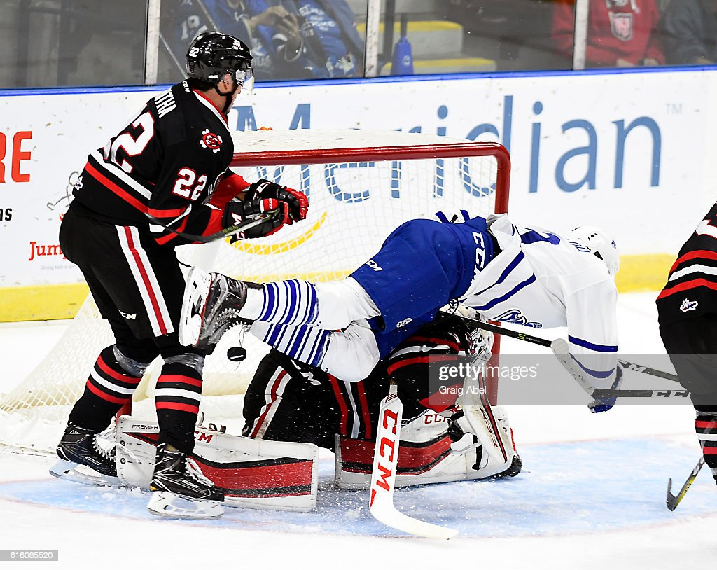 Michael McLeod #9 of the Mississauga Steelheads flies through the crease in front of Ryan Mantha #22 and Colton Incze #31 of the Niagara IceDogs during game action on October 21, 2016 at Hershey Centre in Mississauga, Ontario, Canada.