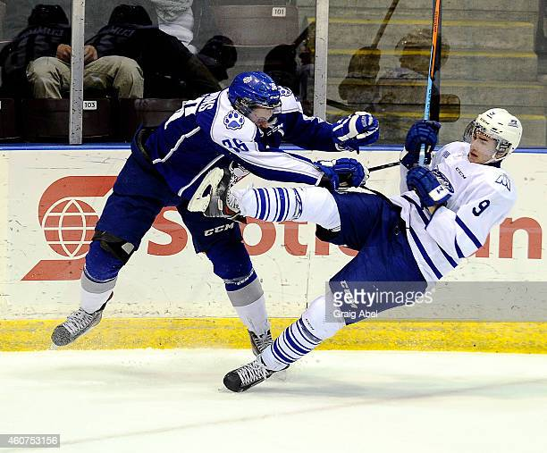 Michael McLeod of the Mississauga Steelheads takes a big hit from Connor Cummins of the Sudbury Wolves during OHL game action on December 21 2014 at...