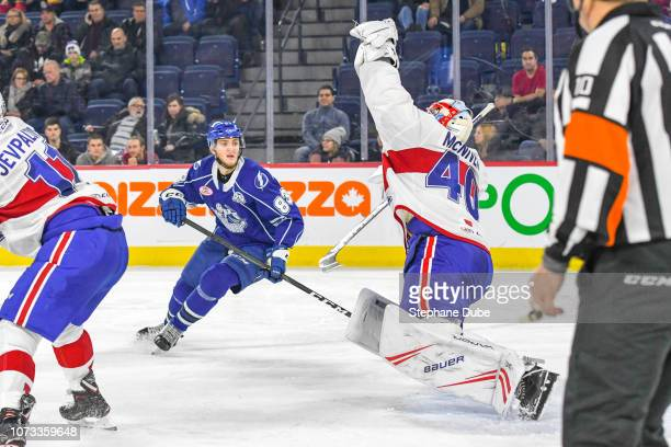 Michael McNiven of the Laval Rocket reaches high to catch the puck with his glove while Alexander Volkov of the Syracuse Crunch looking at the save...
