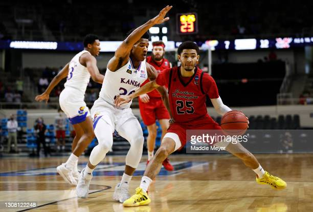 Michael Meadows of the Eastern Washington Eagles drives the ball as Ochai Agbaji of the Kansas Jayhawks defends during the first half in the first...