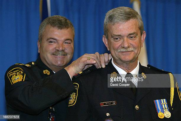 Michael Metcalf, a 32 year veteran of the Peel Regional Police, receives his Deputy Chief epaulettes from Chief Noel Catney during a ceremony...
