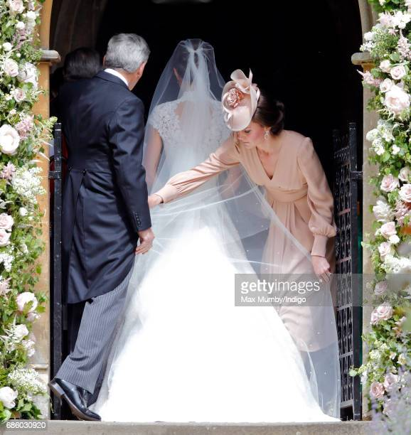 Michael Middleton and Catherine Duchess of Cambridge help Pippa Middleton with her wedding dress as she arrives for her wedding at St Mark's Church...