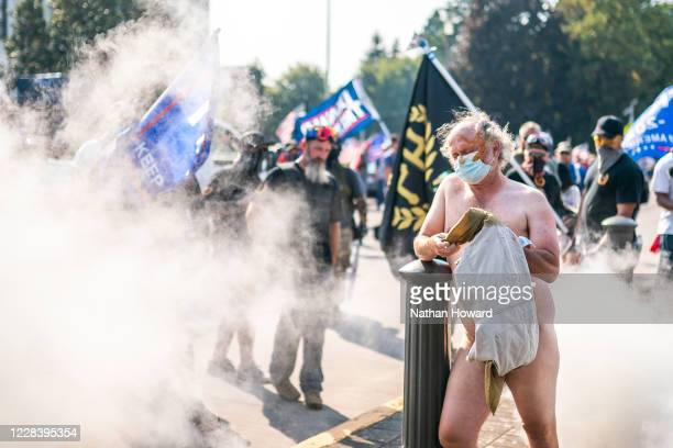 Michael Miller reacts after being pepper sprayed by far-right protesters during a rally on September 7, 2020 in Portland, Oregon. A Pro-Trump caravan...