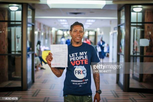 Michael Monfluery who has never been eligible to vote, stands in a courthouse corridor following special court hearing aimed at restoring the right...