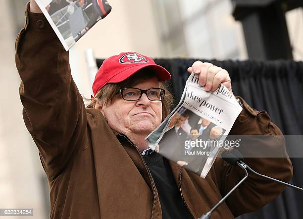 Michael Moore protests Donald Trump's presidency by ripping in half a newspaper with the headline 'Trump takes power' at the rally at the Women's...