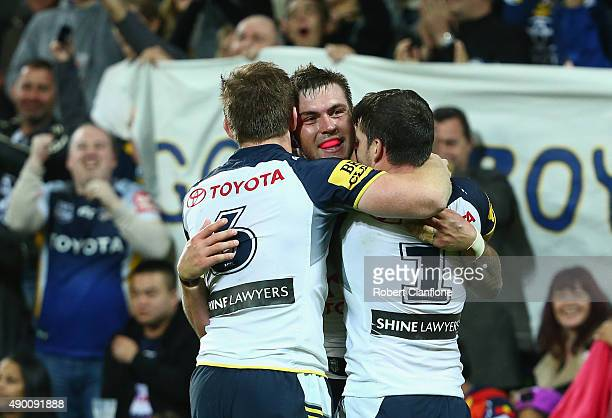 Michael Morgan Kyle Feldt and Lachlan Coote of the Cowboys celebrate after the Cowboys defeated the Storm during the NRL Second Preliminary Final...