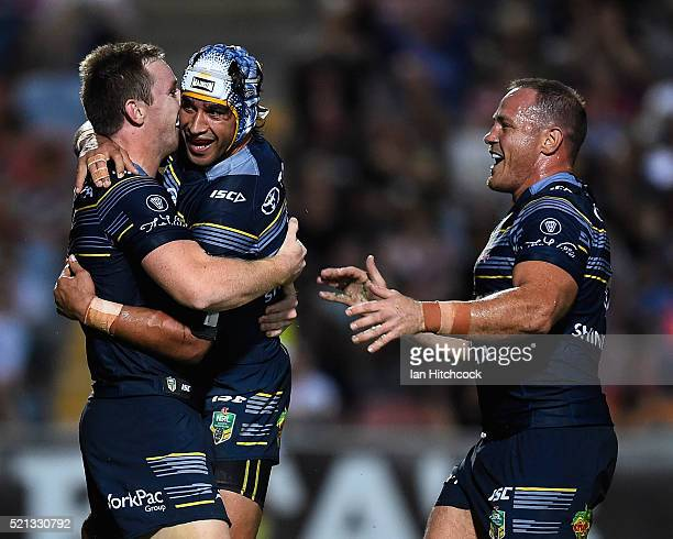 Michael Morgan of the Cowboys celebrates after scoring a try with Johnathan Thurston and Matthew Scott during the round seven NRL match between the...