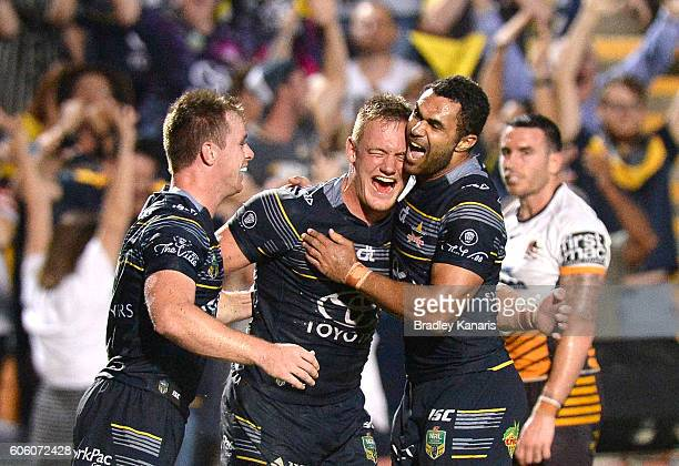 Michael Morgan of the Cowboys celebrates with team mates Justin O'Neill and Coen Hess after scoring a try during the first NRL semi final between...