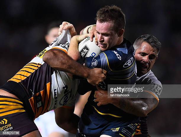 Michael Morgan of the Cowboys is tackled by Corey Parker of the Broncos during the round 11 NRL match between the North Queensland Cowboys and the...