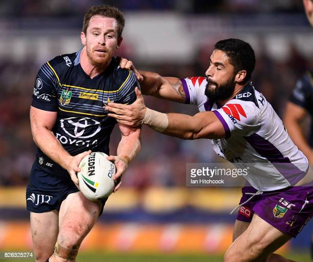 Michael Morgan of the Cowboys is tackled by Jesse Bromwich of the Storm during the round 22 NRL match between the North Queensland Cowboys and the...