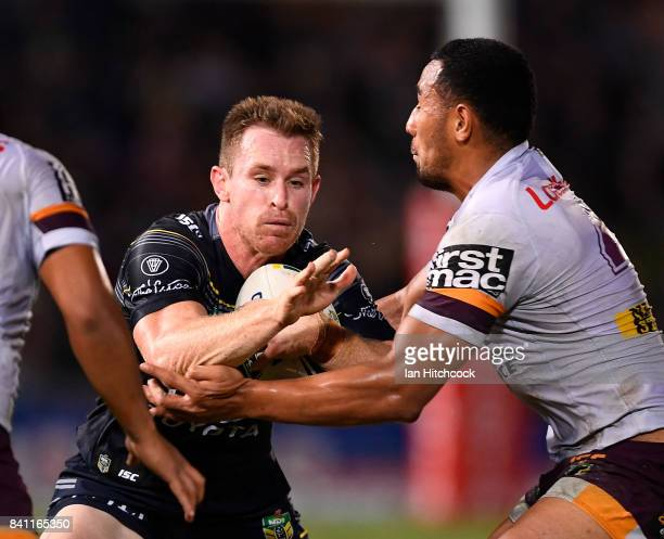 Michael Morgan of the Cowboys is tackled by Tautau Moga of the Broncos during the round 26 NRL match between the North Queensland Cowboys and the...