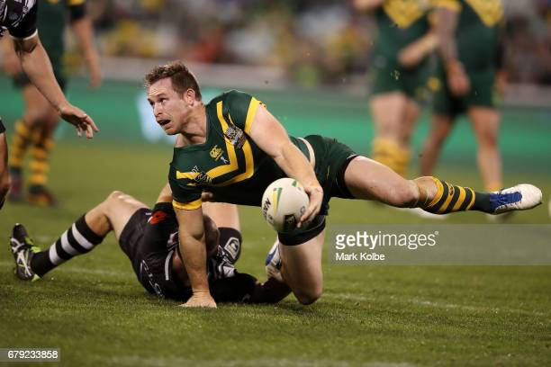 Michael Morgan of the Kangaroos passes as he is tackled during the ANZAC Test match between the Australian Kangaroos and the New Zealand Kiwis at GIO...