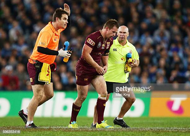 Michael Morgan of the Maroons is assisted from the field after sustaining an injury during game one of the State Of Origin series between the New...