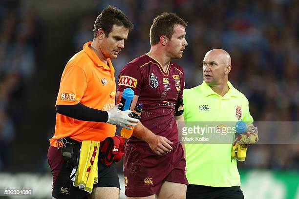 Michael Morgan of the Maroons is assisted off the field during game one of the State Of Origin series between the New South Wales Blues and the...